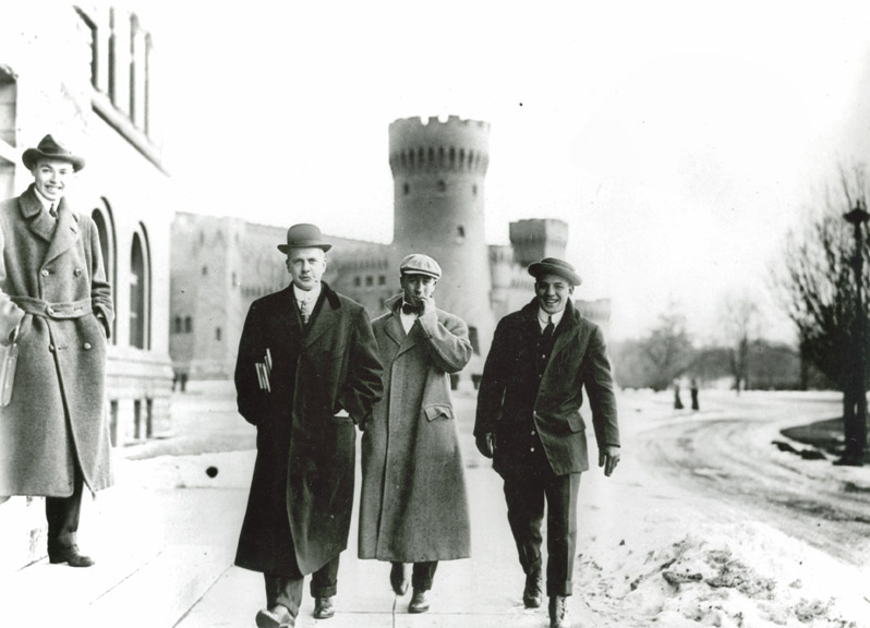 Four students walking around the oval (Armory in background), 1911