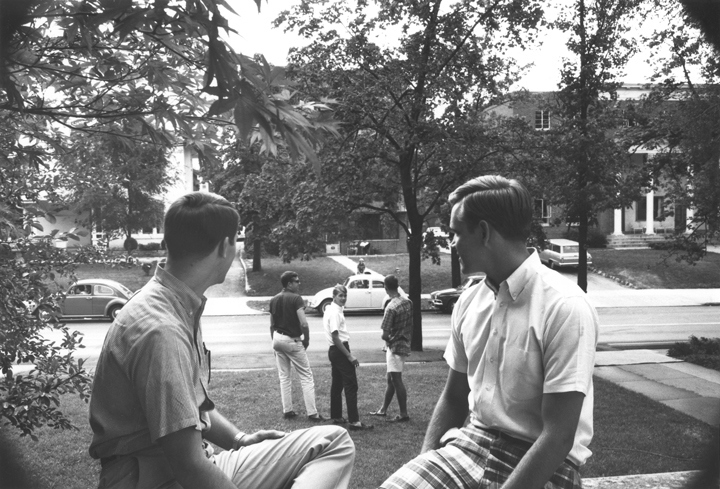 Students chat on a porch on campus