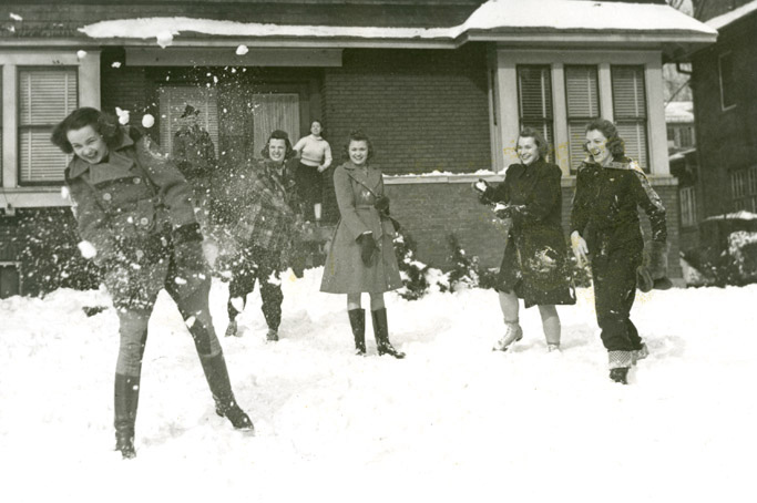 Students have a snowball fight outside of a house