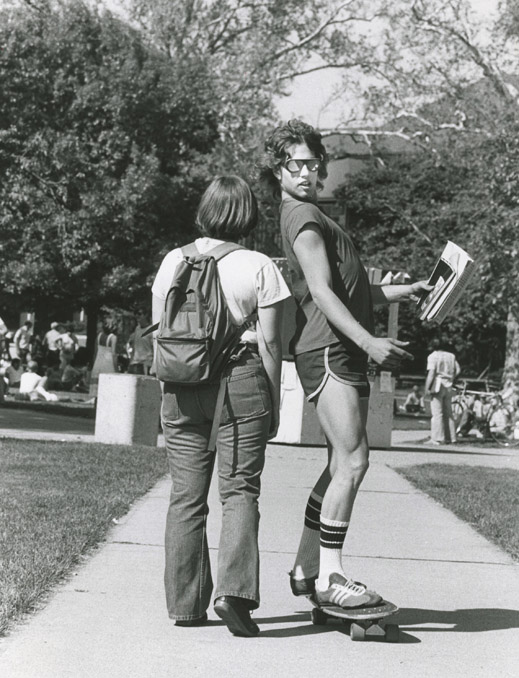 A student skateboards past another student on the oval