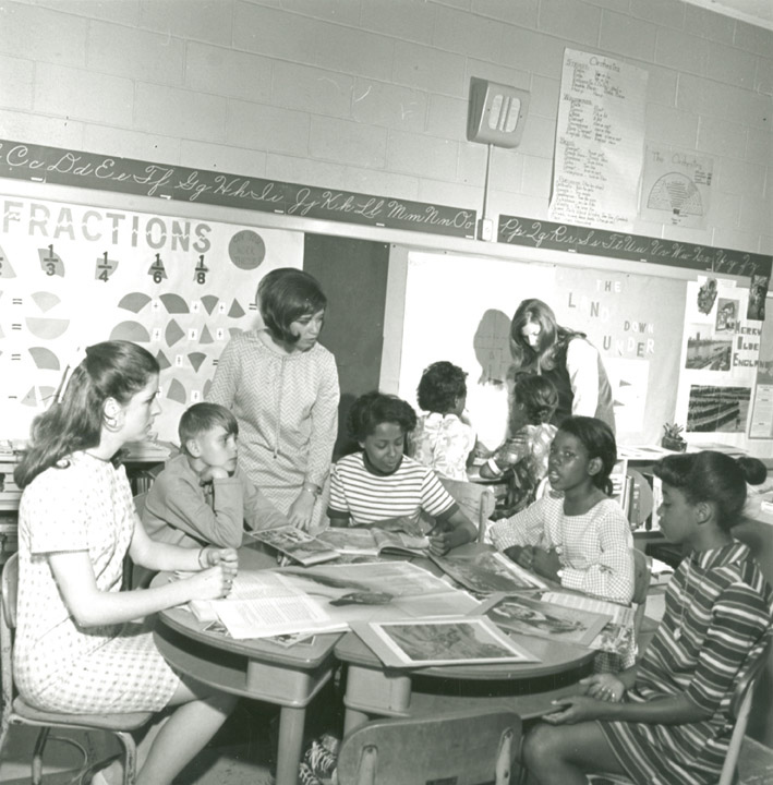A teacher advises students during a group assignment