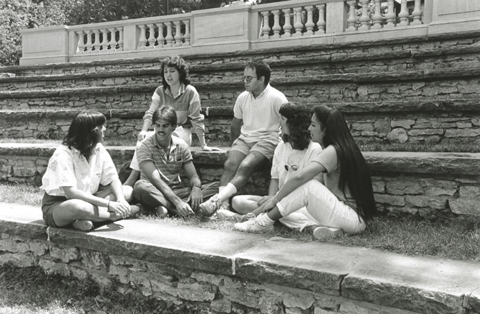 Students sit and talk on steps on campus