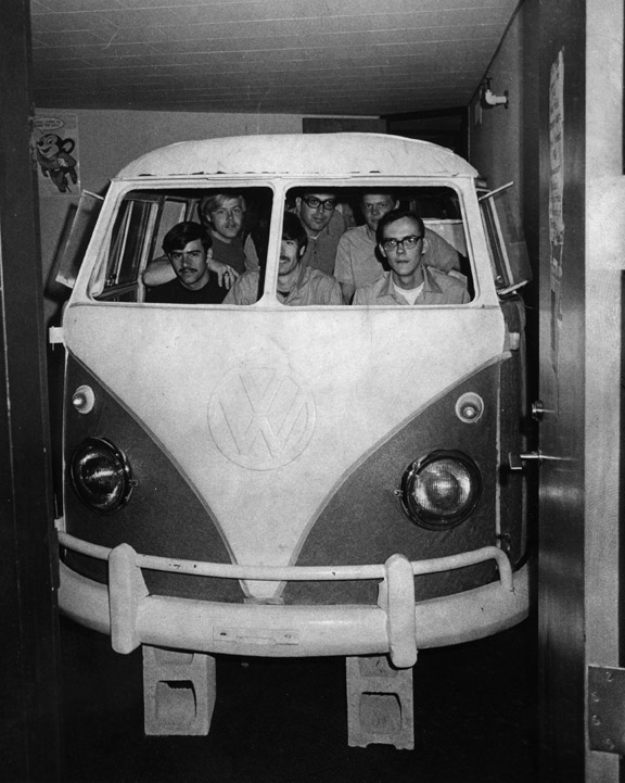 Students sit in a VW bus inside of a room
