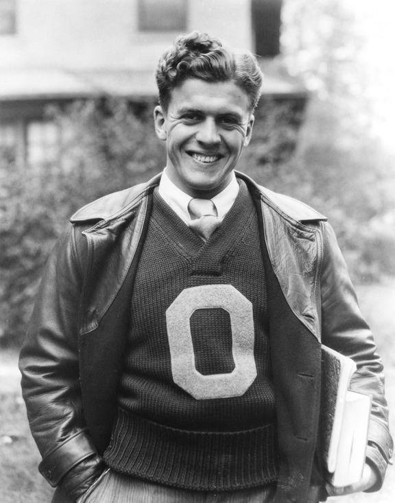 A football player smiles while wearing an Ohio State sweater