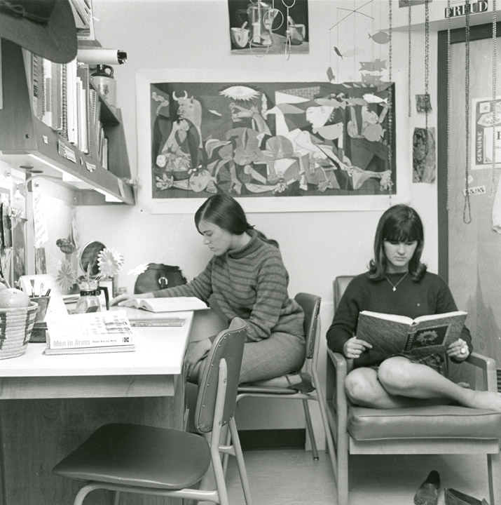 Two students sit and study in a dorm room